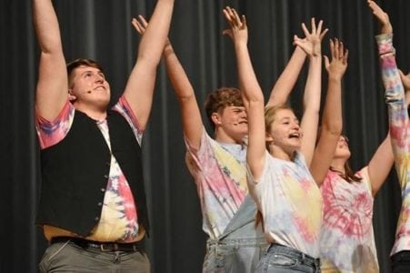 Students with arms raised in a performance